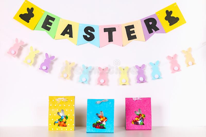 Diy Easter wrapping package sweets in a bag with a cut out bunny silhouette on a white background. Gift idea, decor Spring, Easter. Step by step. Process kid royalty free stock photo