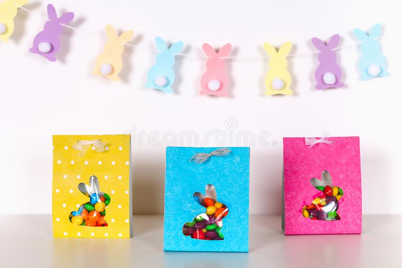 Diy Easter wrapping package sweets in a bag with a cut out bunny silhouette on a white background. Gift idea, decor Spring, Easter. Step by step. Process kid royalty free stock photos