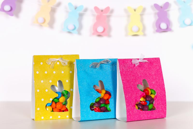 Diy Easter wrapping package sweets in a bag with a cut out bunny silhouette on a white background. Gift idea, decor Spring, Easter. Step by step. Process kid stock photos