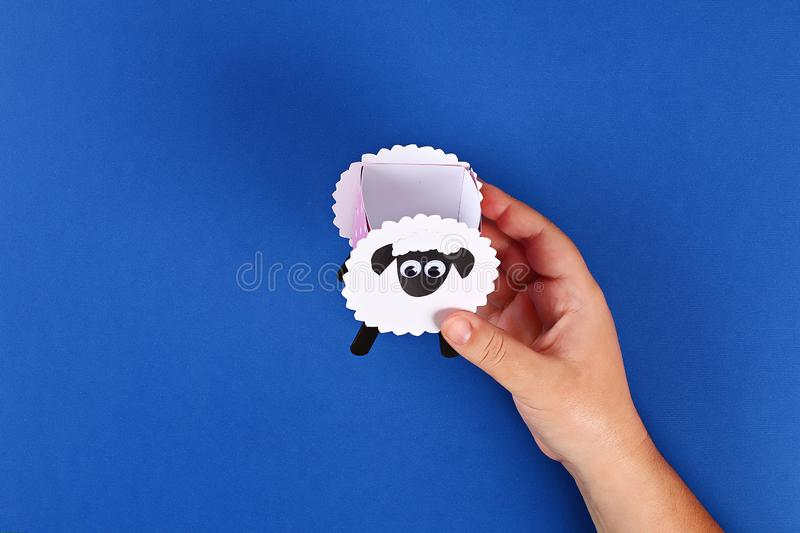 Diy Eid al adha lamb sheep sweet candy paper, wooden sticks for ice cream on blue background stock images