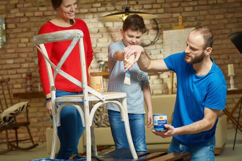 Diy family. Renewing chair at home, father teaching son painting stock image