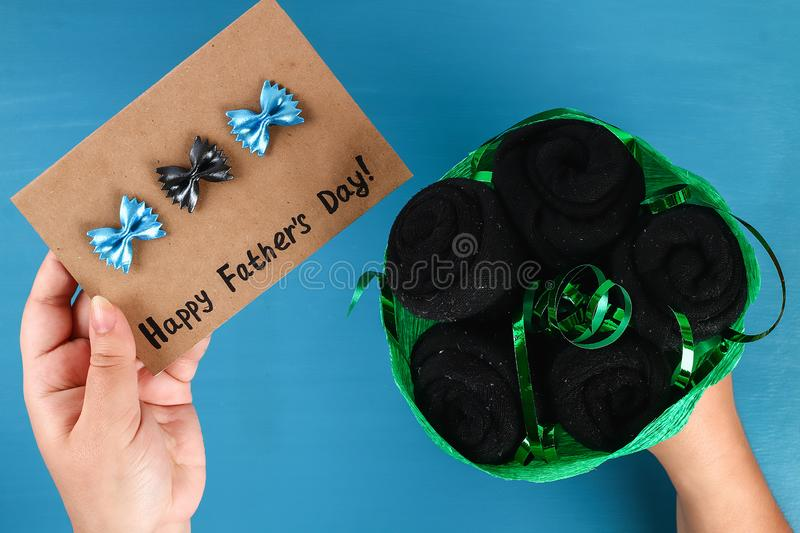 Diy father's day bouquet black roses socks blue background. Gift idea, decor Father day, Daddy. Step by step. Top view. Process kid children craft. Workshop royalty free stock image