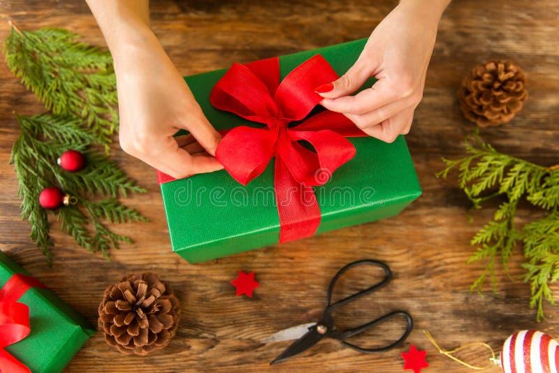 DIY-gåvainpackning Kvinna som slår in härliga julgåvor på den lantliga trätabellen Över huvudet siktsjulinpackning arkivfoton