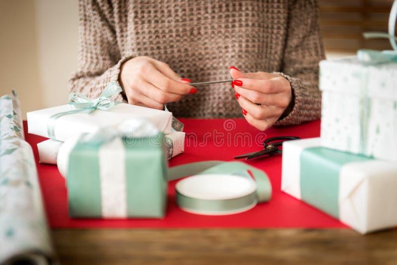 DIY-Geschenk-Verpackung Unrecognisable Frau, die schöne nordische Artweihnachtsgeschenke einwickelt stockfotos