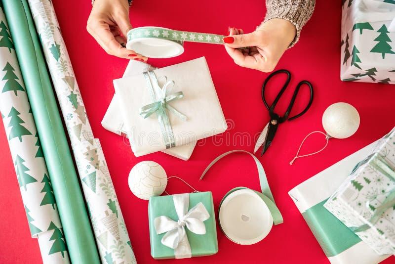 DIY-Geschenk-Verpackung Unrecognisable Frau, die schöne nordische Artweihnachtsgeschenke einwickelt Hände schließen oben lizenzfreie stockfotos