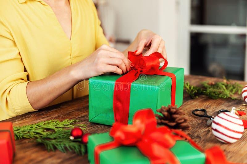 DIY-Geschenk-Verpackung Unrecognisable Frau, die schönes Rot und grüne Weihnachtsgeschenkboxen einwickelt lizenzfreie stockfotografie