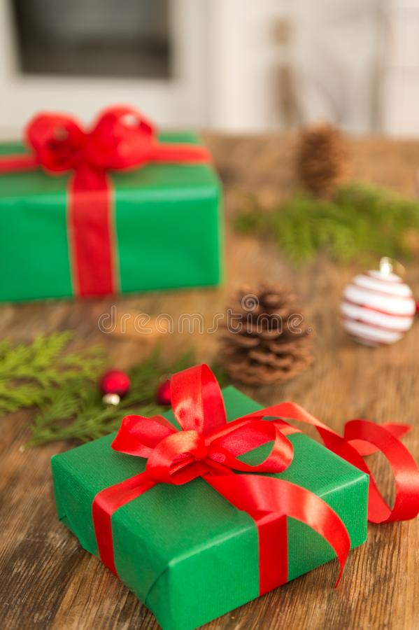 DIY Gift Wrapping. Beautiful green christmas gifts with red bow on rustic wooden table. Christmas presents. stock photos
