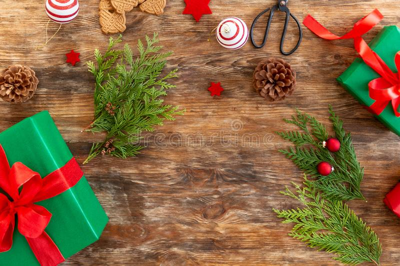 DIY Gift Wrapping. Beautiful green christmas gifts with red bow on rustic wooden table. Top view. stock image