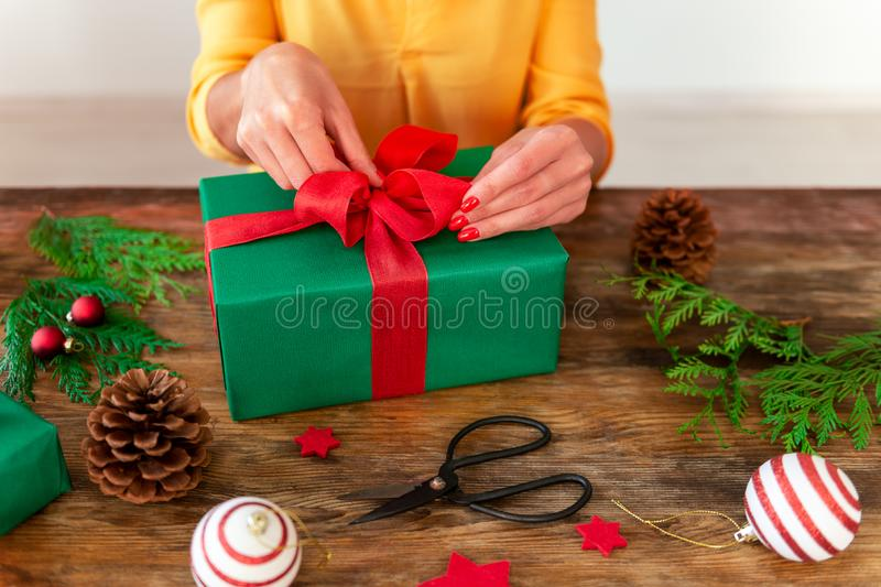 DIY Gift Wrapping. Woman wrapping beautiful christmas gift on rustic wooden table. Cropped shot of christmas wrapping station. stock photos