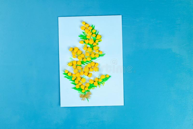 Diy greeting card with mimosa flowers paper balls for March 8 on blue background. Gift idea, decor International Womens Day, March 8, Mother day. Step by step royalty free stock photo
