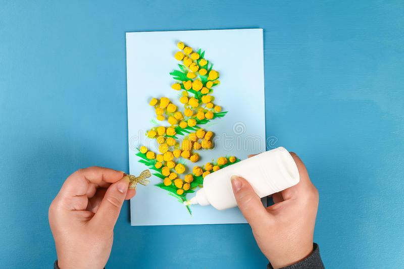 Diy greeting card with mimosa flowers paper balls for March 8 on blue background. Gift idea, decor International Womens Day, March 8, Mother day. Step by step royalty free stock photos
