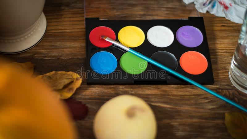 DIY Halloween concept. Art and craft, decorating Halloween pumpkins. Color pallete, paintbrush and pumpkins on a table. DIY Halloween concept. Art and craft stock images