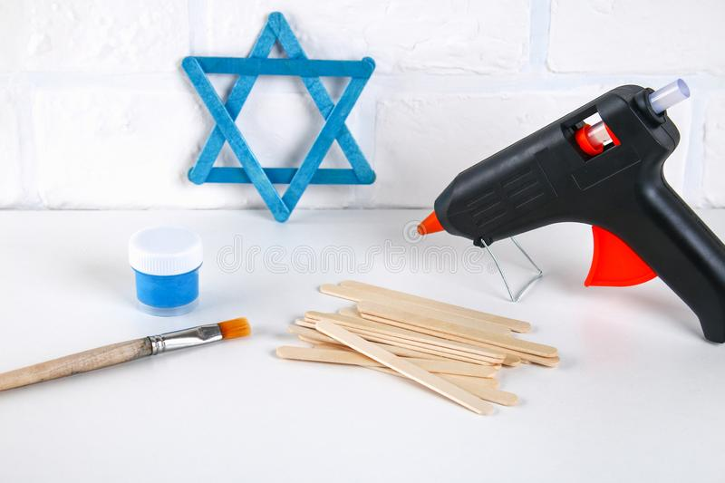 DIY. Hanukkah decor. Star of David from ice cream sticks on a white wooden table. Guide, step by step on the photo. Diy on stock photo