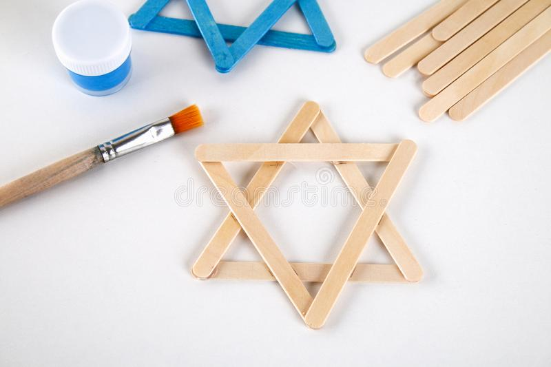 DIY. Hanukkah decor. Star of David from ice cream sticks on a white wooden table. Guide, step by step on the photo. Diy on royalty free stock images