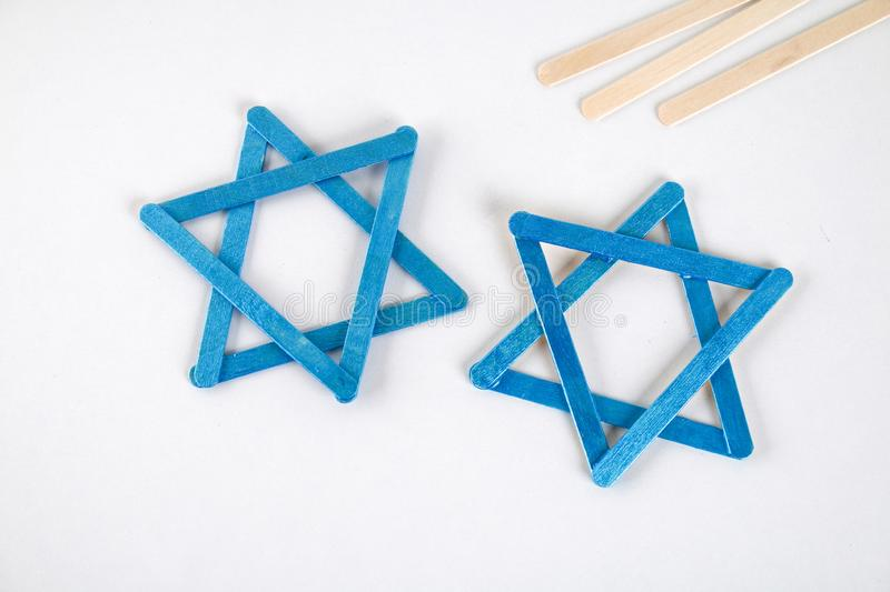 DIY. Hanukkah decor. Star of David from ice cream sticks on a white wooden table. Guide, step by step on the photo. Diy on stock images