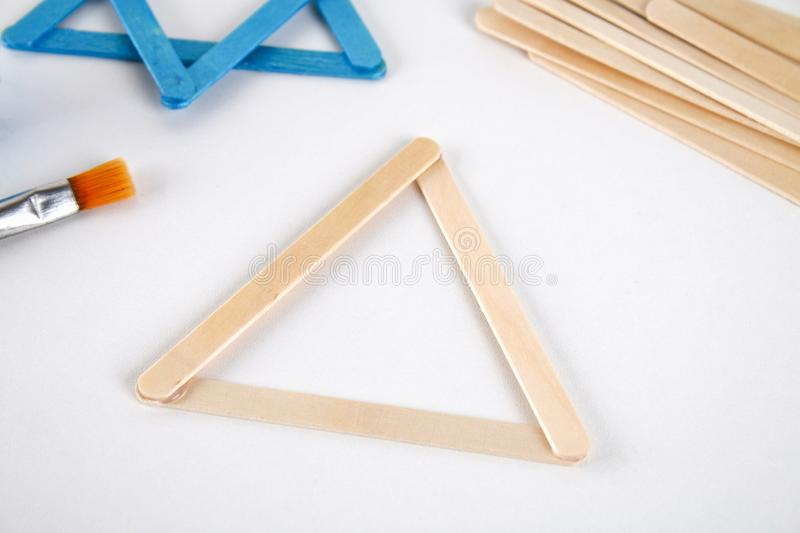 DIY. Hanukkah decor. Star of David from ice cream sticks on a white wooden table. Guide, step by step on the photo. Diy on stock photos