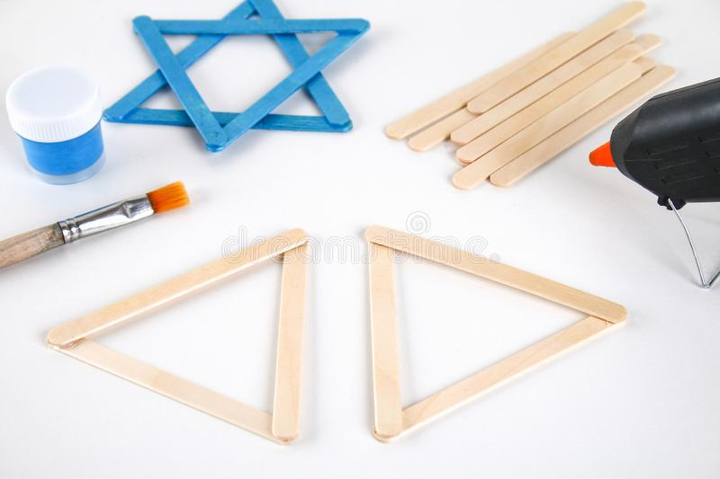 DIY. Hanukkah decor. Star of David from ice cream sticks on a white wooden table. Guide, step by step on the photo. Diy on stock image
