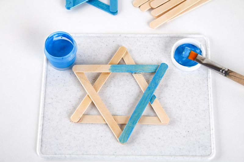 DIY. Hanukkah decor. Star of David from ice cream sticks on a white wooden table. Guide, step by step on the photo. Diy on royalty free stock photos