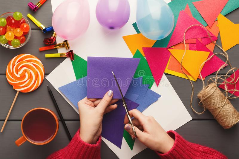 DIY holiday background, birthday party decorations. Birthday handmade background. Female hands making party paper decorations and colorful flags garland. DIY royalty free stock photo