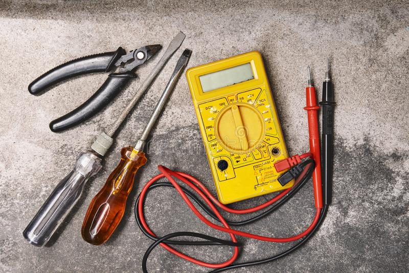 DIY home electricity working tools, screwdrivers, pliers and multimeter on cement background royalty free stock photos