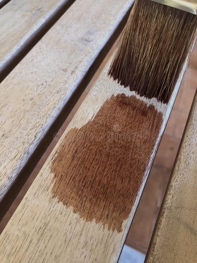 DIY and home improvements, painting furniture. Protecting teak wooden furniture, painting wooden slats with oil, closeup of brush and wood royalty free stock photo