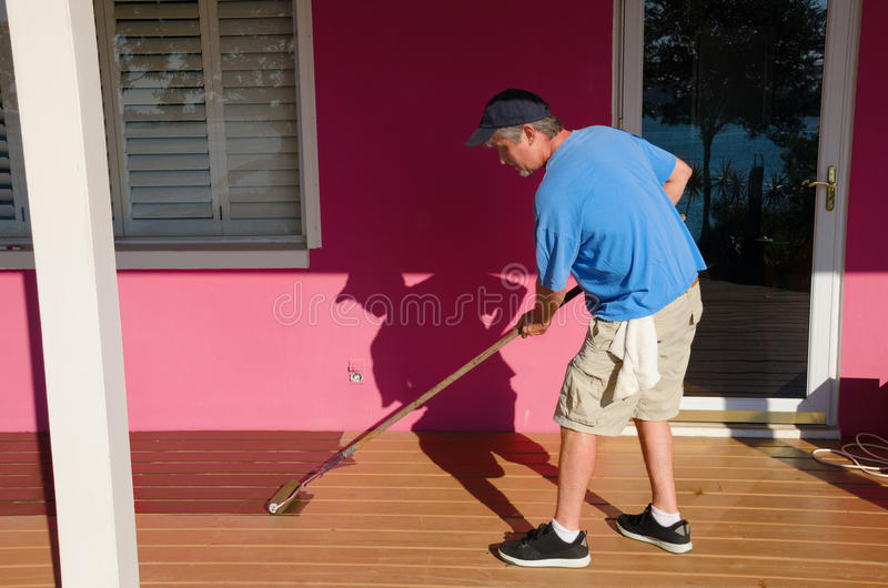 DIY home owner painting staining wooden deck. A DIY do-it-yourself home owner is staining painting a house wooden deck with a long handle paint roller on a sunny royalty free stock photo