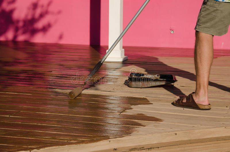 DIY home owner painting staining wooden deck. A DIY do-it-yourself home owner is staining painting a house wooden deck with a long handle paint roller on a sunny stock photos