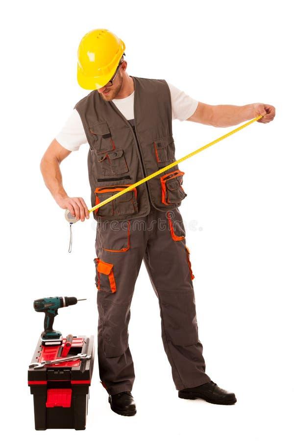 DIY - homem novo que mede com o medidor equipado com o conjunto de ferramentas e o b fotografia de stock royalty free
