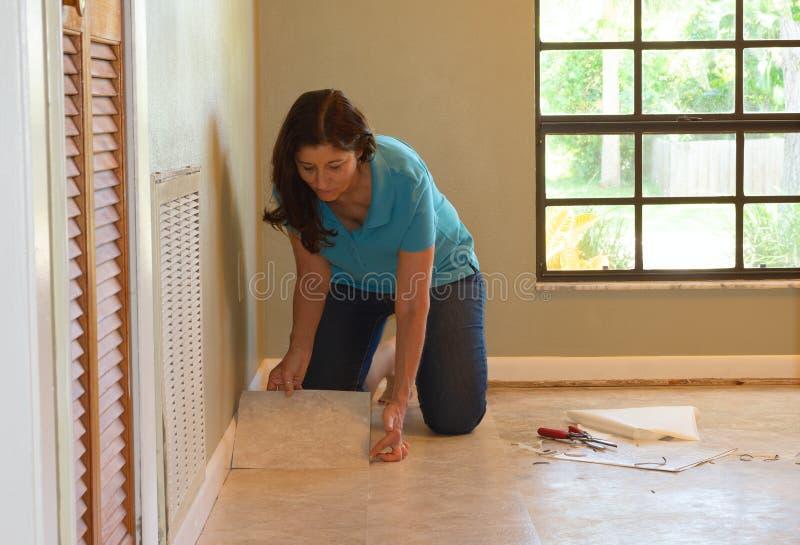 DIY-huiseigenaarvrouw of beroeps die vinyltegelbevloering installeren royalty-vrije stock fotografie