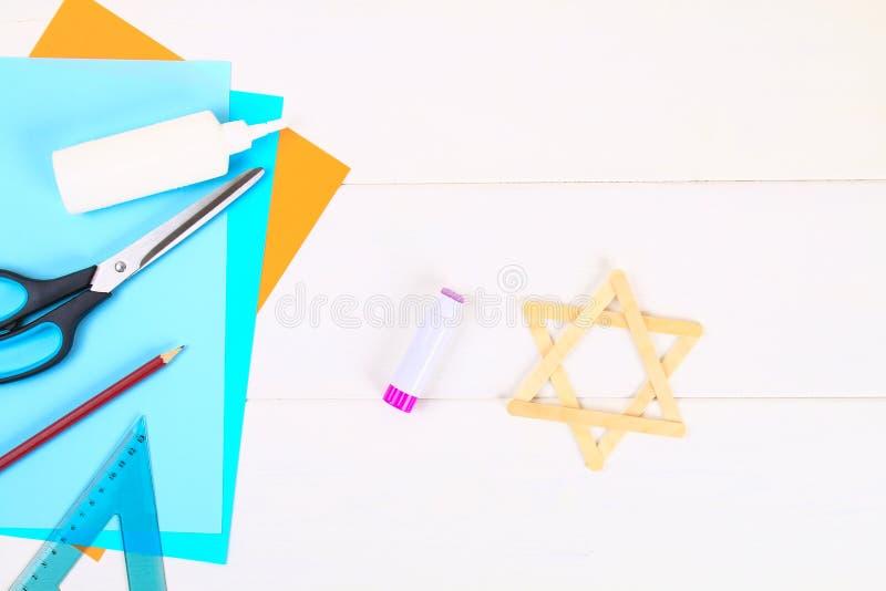 DIY Jodenster met zijn handen van roomijsstokken op een witte houten lijst stock afbeelding