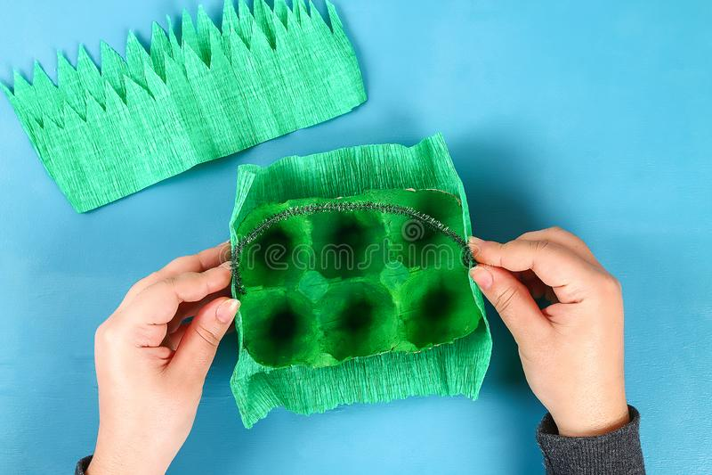 DIY-Korb Osterei vom Pappbehälter, Krepppapier, Chenillestamm auf blauem Hintergrund stockfotos