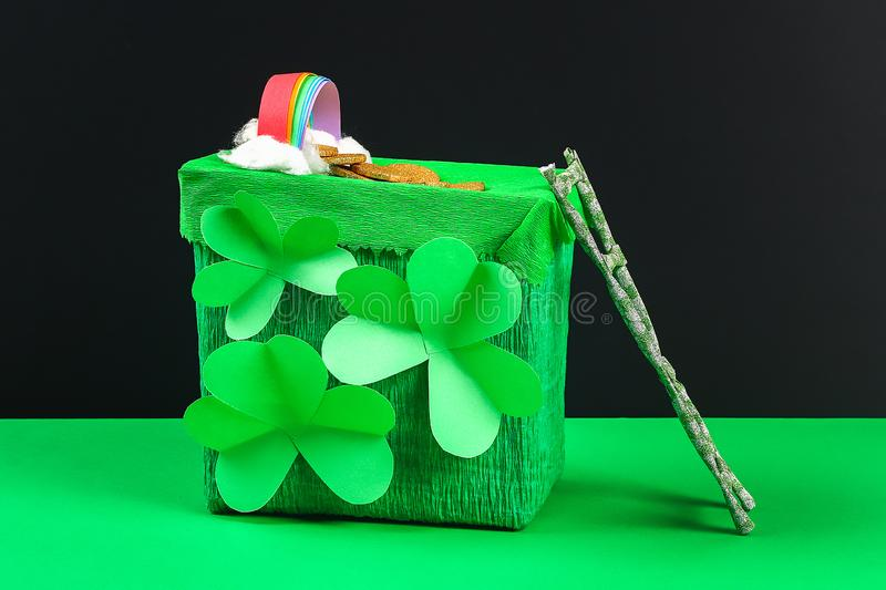 DIY leprechaun trap with gold coins, rainbow and green ladder St Patricks Day background stock photo