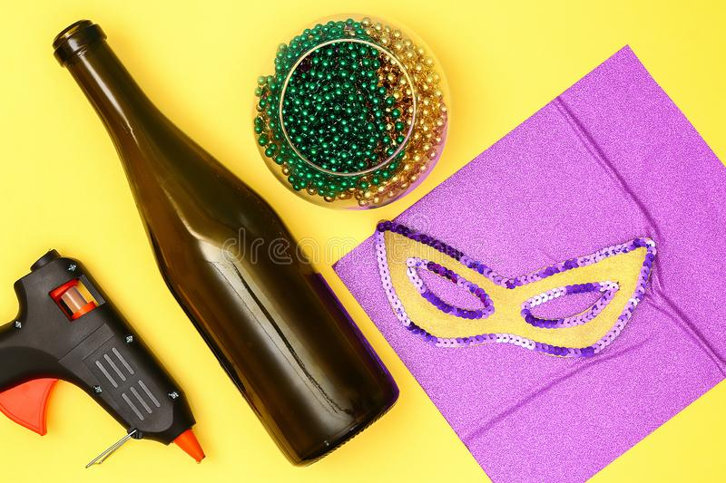 Diy Mardi Gras bottle purple adhesive paper, green bead, carnival mask, sequins yellow background royalty free stock photography