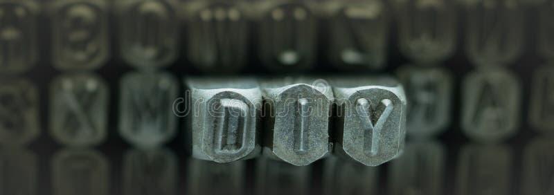 DIY a orthographié du poinçon d'alphabet de timbre en métal, mots de DIY représente le fait vous-même image stock