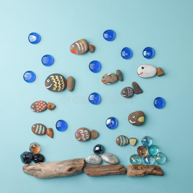 Diy painted stone fish on blue background and sea decoration. Creative DIY idea, surreal imagination kids world. Kid handmade, royalty free stock photos