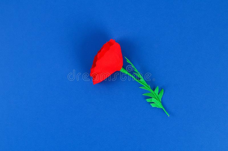 Diy paper red poppy Anzac Day, Remembrance, Remember, Memorial day crepe paper on blue background royalty free stock images