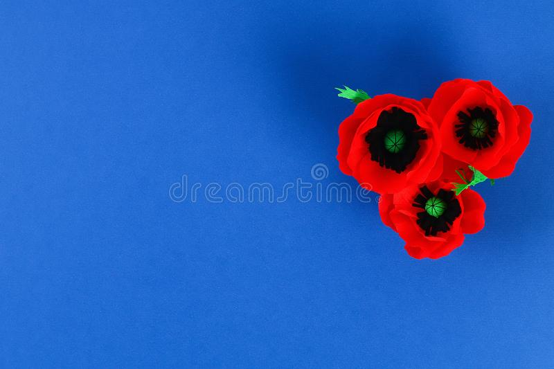 Diy paper red poppy Anzac Day, Remembrance, Remember, Memorial day crepe paper on blue background royalty free stock photos