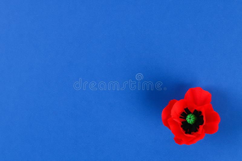 Diy paper red poppy Anzac Day, Remembrance, Remember, Memorial day crepe paper on blue background royalty free stock photography