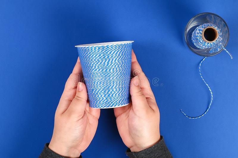 Diy pencil holder plastic glass sour cream, yogurt wrapped thread blue background royalty free stock image