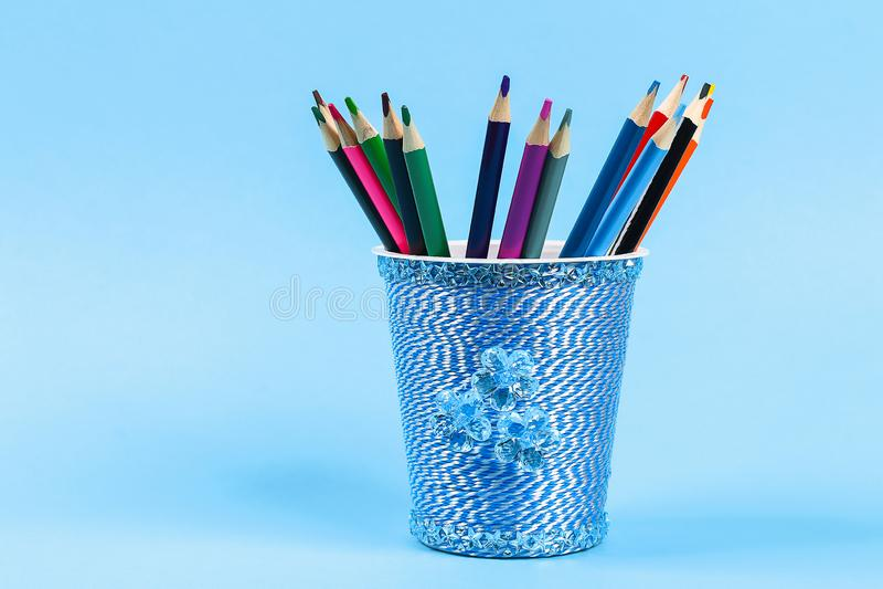 Diy pencil holder plastic glass sour cream, yogurt wrapped thread blue background stock photos