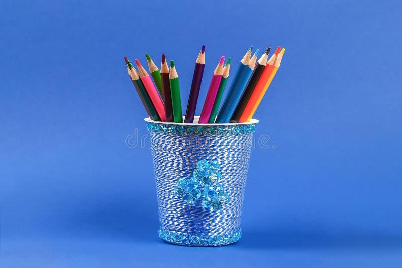 Diy pencil holder plastic glass sour cream, yogurt wrapped thread blue background stock image