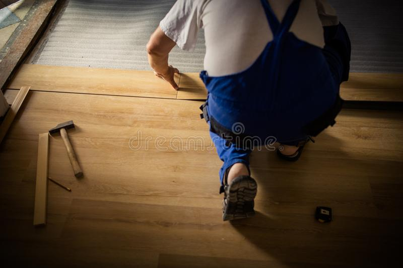 Male lying parquet floor board/laminate flooring. DIY, repair, building and home concept - close up of male hands lying parquet floor board/laminate flooring royalty free stock photography