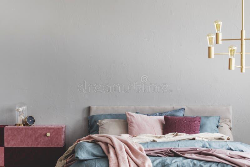 Diy-Samt umfasste Pastellrosa und Burgunder-nightstand nahe bei warmem Bett mit blauer und beige Bettwäsche und rosa Kissen lizenzfreie stockfotografie