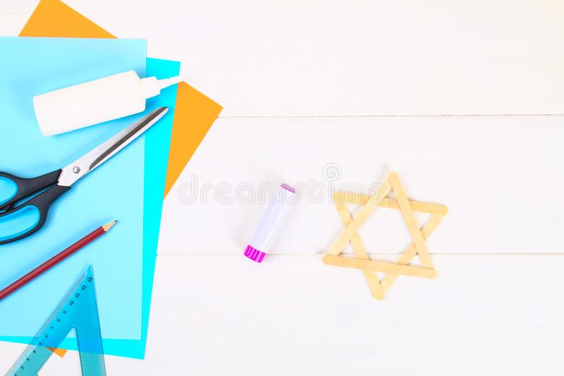 DIY. Star of David with his hands from ice cream sticks on a white wooden table. stock image