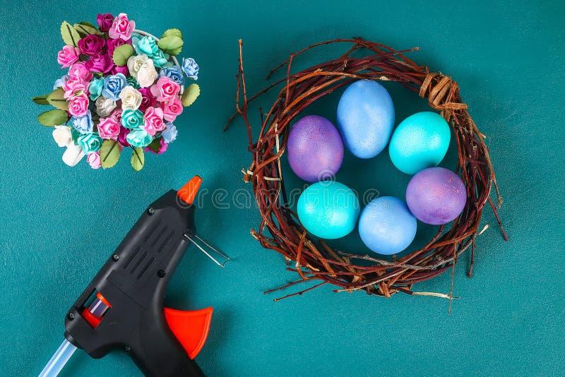Diy Wielkanocny wianek gałązki, malujący jajka i sztuczni kwiaty na zielonym tle, zdjęcie royalty free