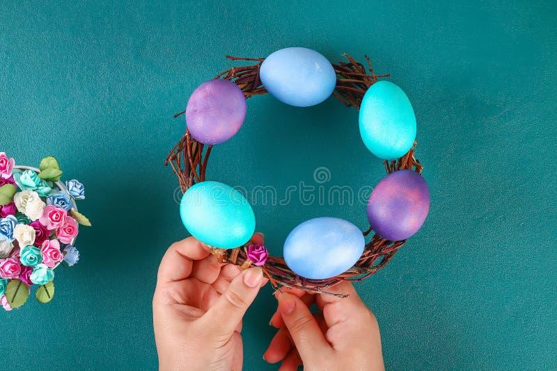 Diy Wielkanocny wianek gałązki, malujący jajka i sztuczni kwiaty na zielonym tle, zdjęcia stock