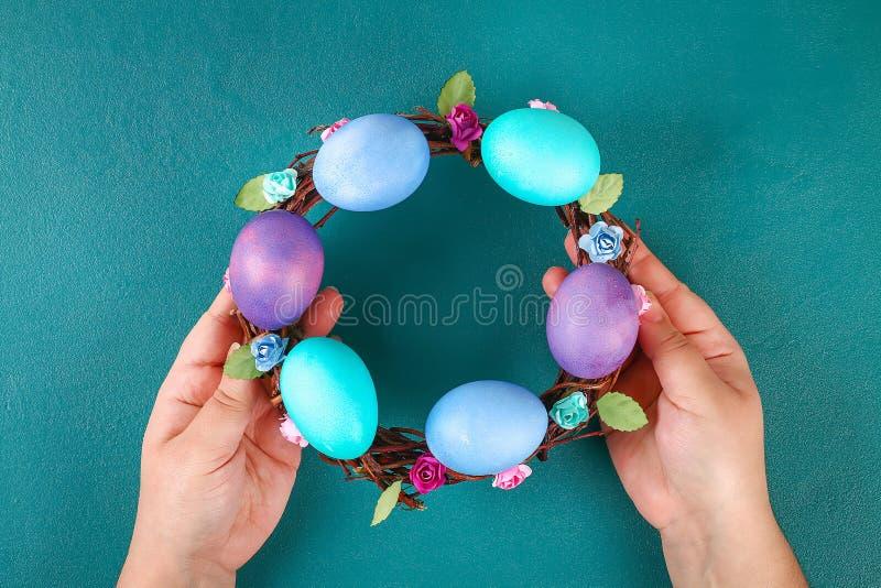 Diy Wielkanocny wianek gałązki, malujący jajka i sztuczni kwiaty na zielonym tle, obrazy royalty free