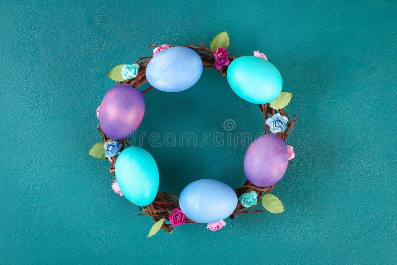Diy Wielkanocny wianek gałązki, malujący jajka i sztuczni kwiaty na zielonym tle, obraz stock