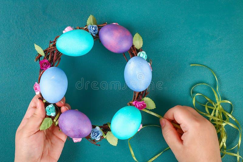 Diy Wielkanocny wianek gałązki, malujący jajka i sztuczni kwiaty na zielonym tle, zdjęcie stock