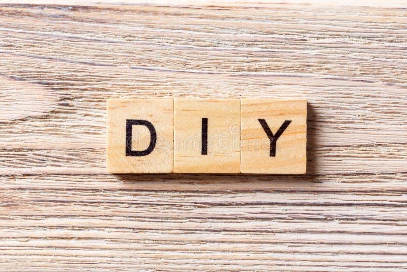 DIY-woord op houtsnede wordt geschreven die Doe het zelf tekst op lijst, concept stock foto's